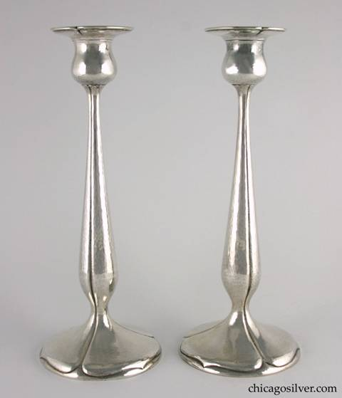 "Kalo candlesticks, tall, pair (2), hammered surfaces with pedestal base, flat bottoms, and tulip form with fluted sides and spade shaped designs on base.  In green cloth KALO bags with yellow stitching.  12"" H and 4-3/4"" W across base and 2-7/8"" W across top.  Marked:  Candlesticks:  STERLING / HAND WROUGHT / AT / THE KALO SHOP / S402.  Bags:  The Kalo Shop / Handwrought Silverware / Chicago"