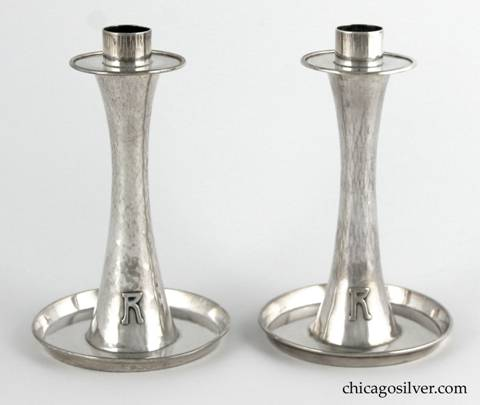 "Kalo hurricane lamps, pair, composed of two candlestick bases plus two removable glass lamps.  The candlesticks have saucer-shaped bottoms with upturned rims, and taper up toward the middle then broaden out again at the top in a figure-8 shape.  The simple bobeche sits above a circular base for the glass lamps.  The tulip-shaped lamps are thin and delicate, and are covered with cut glass designs of two rows with and shapes alternating with lens-like dots.  Candlesticks have applied ""R"" monograms on outside of base.  Candlesticks:  3-3/4"" W at bottom, 2"" W at top and 6"" H.  Lamps:  3-3/4"" W and 6-1/2"" H.  Together:  11-3/4"" H.  Marked:  STERLING / HAND BEATEN / AT / KALO SHOPS / PARK RIDGE / ILLS. / 6197"