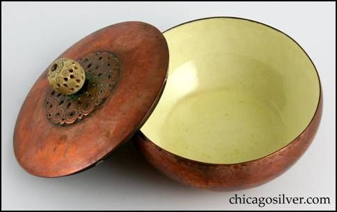Rebecca Cauman bowl, round, copper, with removable lid, white enameled interior and delicately carved and pierced spherical ivory finial on lid atop centered decoration of applied chased concentric circles with pierced small circles and teardrop shapes.