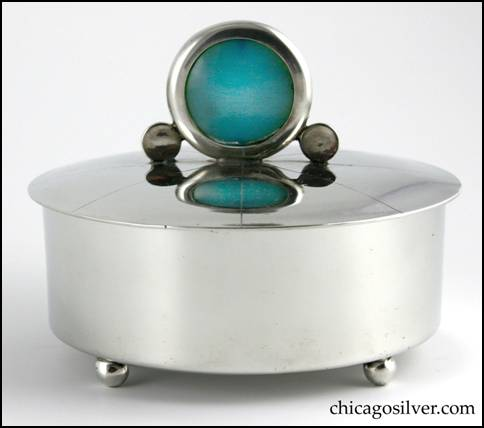 Rebecca Cauman box, round, pewter, straight-sided on flat bottom with four small ball feet, and removable tightly fitted slightly domed lid.  Lid has large upright round translucent blue stone finial in round see-through frame with a small solid round disk on either side, and eight chased lines radiating outward from the center.