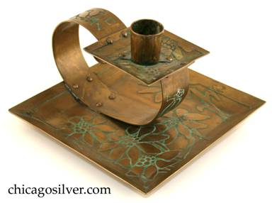 Carence Crafters candleholder, brass, composed of square tray with raised edges riveted to looping strap holding smaller square drip-tray and cylindrical riveted candle-holder.  Surfaces acid etched with floral design.