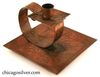 Carence Crafters candleholder, copper, composed of square tray with raised riveted to looping strap holding smaller square drip-tray and cylindrical candle-holder.  Surfaces acid etched with floral design.