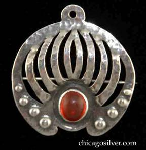Forest Craft Guild brooch, round, German silver, with small tab at top with hole for chain, plus pin with safety clasp at back, nine grill-like curving cutouts below the tab, several graduated repousse domes on bottom edges, and large oval bezel-set red cabochon stone at bottom center.