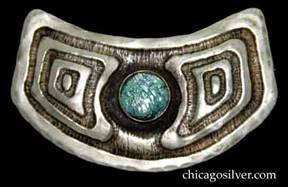 Forest Craft Guild brooch, shield-shaped, German silver, centering round glass cabochon stone with iridescent blue-green enamel foil underneath, chased patterns of concentric squares on each side and around border.