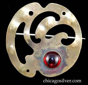 Forest Craft Guild brooch, round, brass, with notches top and bottom, three curving cutouts at center, three pierced holes around edge, and round red bezel-set cabochon stone at bottom.