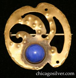 Forest Craft Guild brooch, brass, with notches top and bottom, three curving cutouts at center, two pierced holes around edge, numerous small repousse round domes, and round blue bezel-set cabochon stone at bottom.