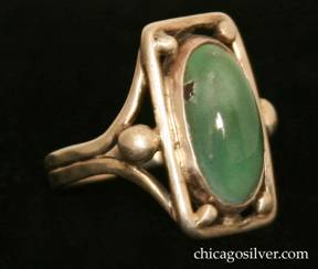 Forest Craft Guild ring, with large rectangular silver frame centering an oval mottled green bezel-set cabochon turquoise stone, four silver beads at the inside corners, and two larger beads outside the frame at the sides.  Split shank.