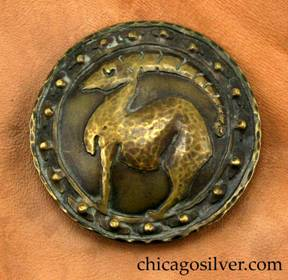 Forest Craft Guild brooch with original tan ooze leather backing.  Brass, round, with dark patina, wide circular decoration on edge of two concentric rings with 18 repouss� dimples between them in mushroom-shaped forms, centering a lifelike rendering of a full-body ibex, with long notched horns and arched back.  Brooch is pinned to original brown ooze leather presentation material.  Hammered edges.