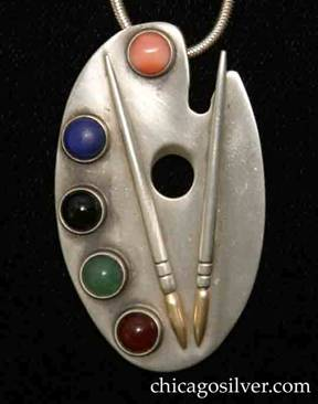 Laurence Foss pendant on chain, in the form of an artist palette, with notched side, five round bezel-set cabochon stones (carnelian, chrysoprase, onyx, lapis, and coral) representing paints, and two chased lifelike applied silver paintbrushes on either side of thumb hole with 14K gold brush tips.  Pin on back for use as brooch.