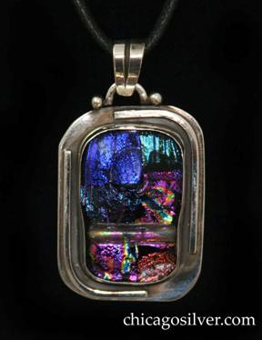 Laurence Foss pendant on cord, rectangular with rounded corners, wide silver frame centering rectangular bezel-set thick handmade iridescent glass stone with rounded corners.  Applied curving wire ornament around top right and lower left part of frame.  Semicircular loop applied to top with bead at each end, and chased moveable bale.  On black leather cord with key-like fastener.