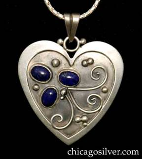 Laurence Foss pendant on chain, in the form of a heart, with raised border, oxidized background, and three oval bezel-set cabochon lapis stones and curving bead and wirework.