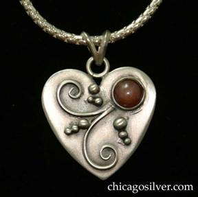 Laurence Foss pendant on chain, in the form of a small heart, with oxidized background, bead and curving wirework ornament, and bezel-set cabochon carnelian stone.