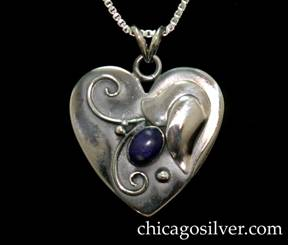 "Laurence Foss pendant on chain, in the form of a small heart, with oxidized background, applied flower, bead and curving wirework ornament, and bezel-set oval cabochon lapis stone.  While most Foss jewelry has a soft ""brushed"" surface, this pendant is highly polished."