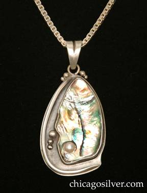 Laurence Foss pendant on chain, in a freeform teardrop shape, with an oxidized background, thick applied wire curving around on the left and bottom edges, applied beads at the top on either side of the bale ring, and a large freeform teardrop-shape bezel-set iridescent green/pink/blue paua shell in the center and right side, with a pearl inset into a small hole at the bottom of the shell, and applied beads to the left of it.  Heavy.