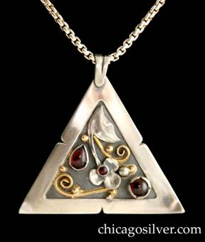 Laurence Foss pendant on chain, triangular, with fixed and chased bale at top.  Wide notched silver frame with corners that curve forward, around incised oxidized interior with gold beads and curving wires, and detailed applied silver leaf and blossom.  Bezel-set teardrop garnet on the left, round bezel-set garnet with notched frame on the right, and small round bezel-set garnet in the center of the blossom.  On box chain.