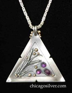 Laurence Foss pendant on chain, triangular, with fixed bale at top surrounded by three successively smaller gold beads on each side.  Wide frame with small notches in the middle of each side, around incised oxidized interior with gold beads, and detailed applied sawtooth leaves and cattails.  Three rich purple cabochon bezel-set amethyst stones at one corner.  On very thick intricate boxlike chain.