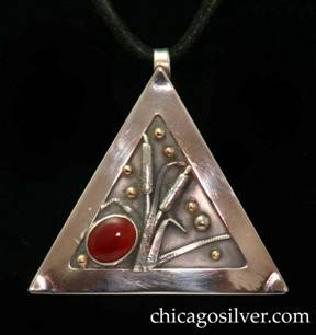 Laurence Foss pendant on cord, triangular, with fixed bale at top.  Wide silver frame around incised oxidized interior with gold beads, and detailed applied worked silver leaves and cattails.  Large diagonal oval cabochon bezel-set red stone at one corner.  On black leather cord with key-like fastener.