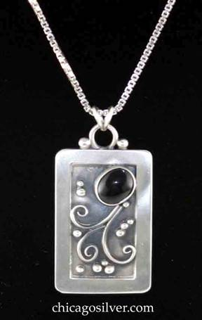 Laurence Foss pendant on chain, rectangular, with rounded corners and fixed round bale on top with small silver bead on each side.  Wide frame around incised oxidized interior with silver bead and curving wire ornament and dark black oval cabochon bezel-set stone at angle near top.  On Venetian box chain.