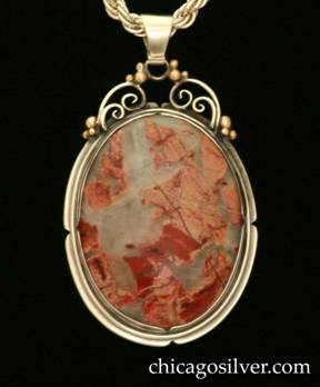 Foss pendant on chain.  Large oval bezel-set transparent cabochon milky white stone with dark and light red inclusions inside notched bezel and frame.  Spiraling silver wirework and gold beads at the top supporting the bale.  Heavy silver chain.