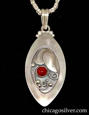 Foss pendant on chain, oval, with pointed ends and wide raised edge, oxidized background, applied stylized tulip with silver beads and curving wirework ornament, and round red bezel-set carnelian stone.
