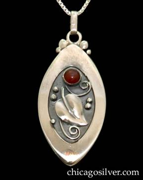 "Foss pendant on chain, oval, with pointed ends and wide raised edge, oxidized background, applied leaf with silver beads and curving wirework ornament, and round red bezel-set stone.  While most Foss jewelry has a soft ""brushed"" surface, this pendant is highly polished."