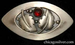 Foss brooch, oval, with pointed ends, wide raised edge, two applied serrated leaves with curving central vein, silver beads, oxidized background, and round red bezel-set garnet stone.