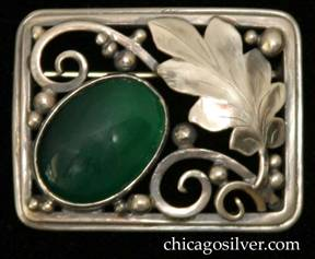 Laurence Foss brooch, rectangular, on silver wire frame with rounded corners, large chased and serrated oak leaf at the upper right corner and a perpendicular angled bezel-set cabochon oval deep green onyx stone at the lower left corner, with applied beads and thick wirework decoration.  Very much in the style of Edward Oakes.