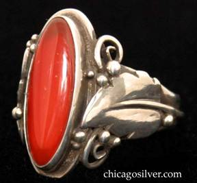 Laurence Foss ring, silver, with large slender oval vertical bezel-set cabochon carnelian stone in oxidized frame surrounded by an applied serrated leaf with a prominent central vein and beads and wirework decoration on each side.  A wire runs around the back of the ring connecting the bottoms of each leaf stem