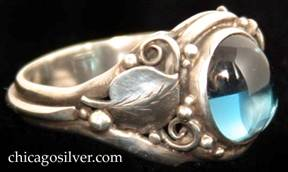 Laurence Foss ring, silver, delicate, with oval bezel-set cabochon light blue topaz stone set at a slight angle in oxidized frame surrounded by a smooth applied leaf with chased details and beads and wirework decoration on each side.  A wire runs around the back of the ring connecting the bottoms of each leaf stem.