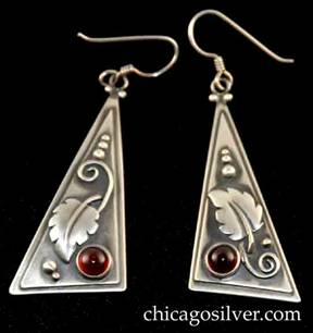 Laurence Foss earrings, pair (2), for pierced ears, with long wire hooks, slightly convex bodies in the form of long thin right-triangles with smaller triangle applied over slightly larger one.  Silver bead and curving wirework ornament on oxidized background and applied leaf with strong central spine and spiraling stem.  Deep red cabochon bezel-set garnet stone at one corner.
