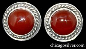 Laurence Foss earrings, pair (2), for pierced ears, round button-form, each with twisted ropelike frame centering a round bezel-set cabochon carnelian stone.  Small pin extending from center of back.