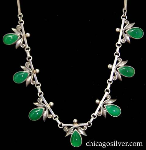 Laurence Foss necklace composed of ten bar links and seven links with teardrop-shaped green bezel-set cabochon stones below scrolling ornament with stylized leaves, and small bead at very top.   Links with stones and intermediate links are bar-shaped and joined to each other with small round silver loops.