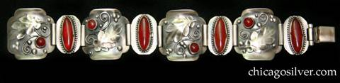 Laurence Foss bracelet, with carnelians.  Four large square convex links alternating with four smaller oval flat ones.  The large links have curved corners, and tops and bottoms that curve upward, with a large applied oak leaf, a small round cabochon bezel-set carnelian stone, and bead and curving wirework detail on each.  The small links have large oval bezel-set cabochon carnelian stones on each, with notched bezels and a thin beaded wire ornament surrounding the bezel.  Links are joined with wide silver tubes.  The piece has many Oakes-type details.