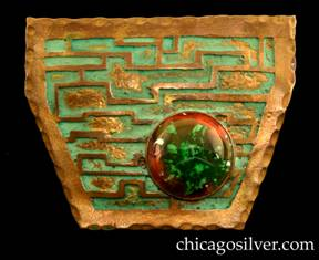 Frost Workshop brooch, brass, shield-shaped with six straight sides, with a wide top and narrow bottom, gilded hammered edge, and a gold maze of narrow lines against a blue-green verdigris background with applied splotches of gilding, and a large round bezel-set red and green glass cabochon stone in the lower right-hand corner.