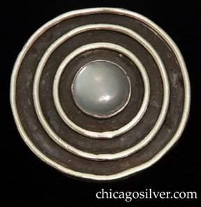 Mary Gage brooch / pin, circular frame with open back and three concentric thick rings on front centering a bezel-set cabochon moonstone.  Outermost circle is somewhat irregular.  Heavy.