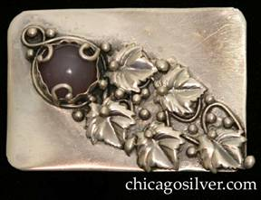 Mary Gage pin, rectangular, with rounded corners, and applied diagonal pattern of leaves, vines, and beads moving down from upper left to lower right, with a bezel-set round purple cabochon stone at top left secured by three silver loops ending with small beads
