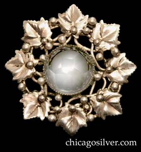 Mary Gage pin, round, composed of a circle of eight chased leaves surrounding a central cabochon clear round crystal or quartz stone