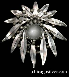 Mary Gage pin, round, composed of a wreath of long, thin outward-pointing chased leaves on a circular frame strengthened with irregular wirework beneath, centering a large clear bezel-set rock crystal stone