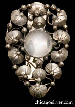 Mary Gage dress clip, tapered shield-shaped form centering a round bezel-set clear rock crystal stone surrounded by small chased lily pads, vines, and applied silver beads