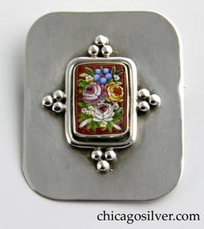 Lillian Pines brooch / pin, silver, flat and rectangular with rounded corners, centering a bezel-set rectangular micro-mosaic of a flower arrangement in a red background, with a heavy round applied wire encircling the bezel and four evenly spaced groups of three applied silver beads around the wire.