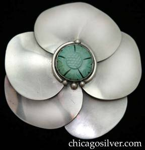 Lillian Pines brooch / pin, large, round, in the shape of a stylized flower blossom, composed of smooth overlapping petals separated by small silver beads, and centering a carved bezel-set turquoise or jade blossom inside a silver ring ornamented with silver beads.