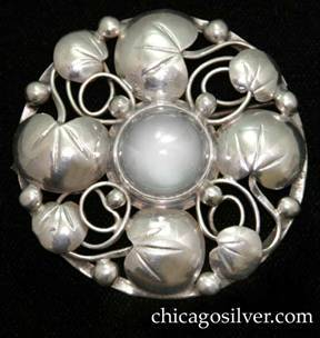 Lillian Pines brooch / pin, round with four large chased lily pads interspersed with four smaller ones, surrounding a central bezel-set round clear cabochon stone, with applied beads and vines on a round frame.