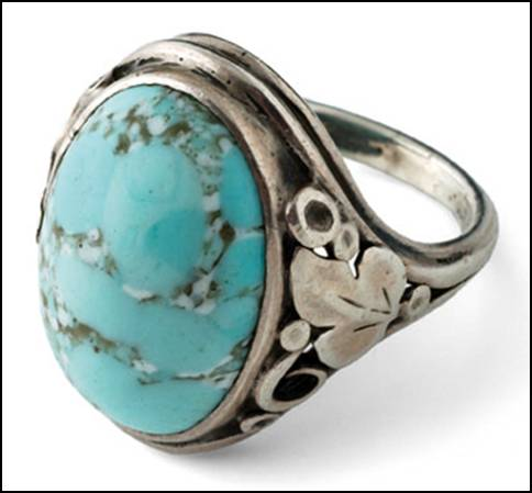 Ring by Gilbert Oakes, hand wrought in sterling silver, size 5-1/2 with a light blue turquoise cabochon with matrix (sky blue) flower, leaf, bead and scroll work on either side of shank. The right side is different from the left.  Unsigned.