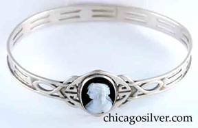 Kalo bracelet, bangle, with oval white cameo of woman facing left on a black background, on an elaborate wirework Celtic knot with small internal cutouts, with two repeated pairs of trapezoidal cutouts encircling the band, and applied wire to the top and bottom of the band.