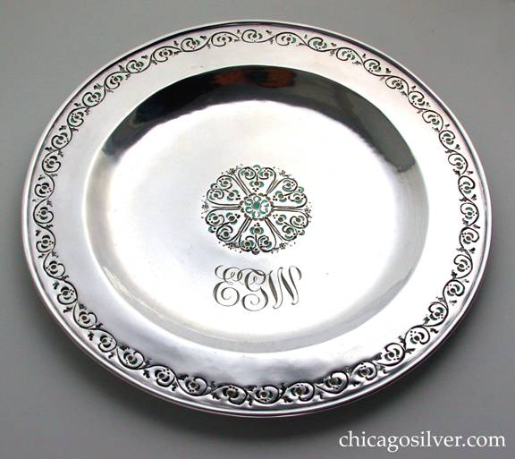 Mary Catherine Knight plate, round, enameled, with chased decoration of flowers and vines around the raised rim and in a central petal-like decoration, with green and pale yellow enamel and engraved EGW monogram in script.