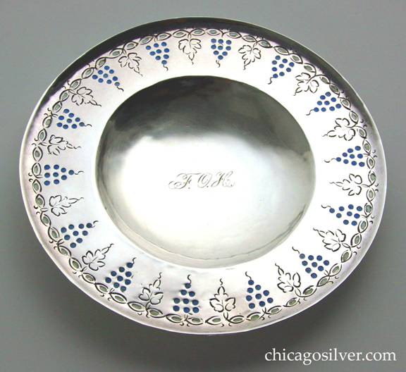 Mary Catherine Knight plate, round, enameled, on small ring foot, with chased decoration or grapes and leaves and stylized vines around the upturned edge.  Engraved FOH monogram in script at concave center.
