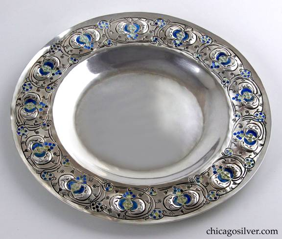 Mary Catherine Knight plate, low, round, enameled, flat bottom, with chased floral and abstract semi-circular decoration of blue and cream-colored enamel around wide flat raised edge.  Heavy and in very good shape.  Enamel is in excellent condition.