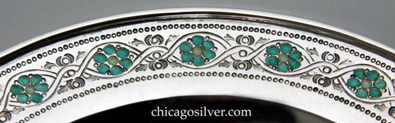 Closeup of Mary Catherine Knight bowl, low, round, enameled, on flat foot, with chased decoration of intertwined vines and teal enameled flowers with cream-colored centers around the edge, and a smaller ring of these around the bottom.  Applied thick wire to rim.  Heavy and in excellent shape.  Enamel is in excellent condition.