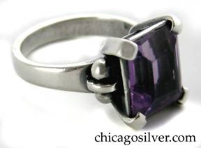 Kalo ring, handwrought in sterling silver with large rectangular cut amethyst in a prong setting with a bar and ball decoration on shank, flanking the stone on either side.