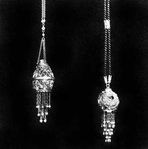 Two pendants, one in form of lantern tipped with baroque pearl suspended  on simple chain; the other elaborately wrought foliated design on gold base, suspended on black cord, by Edward E. Oakes